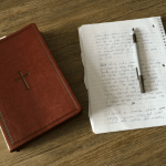 A picture of the Bible and a notepad and pen